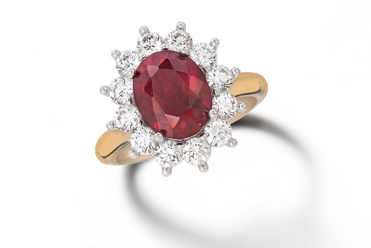 Rubylicious! A stunning oval ruby  engagement ring surrounded by diamonds in white and yellow gold.