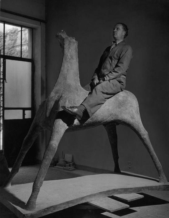 Marino Marini in Milan in his studio at the turn of one of his sculptures