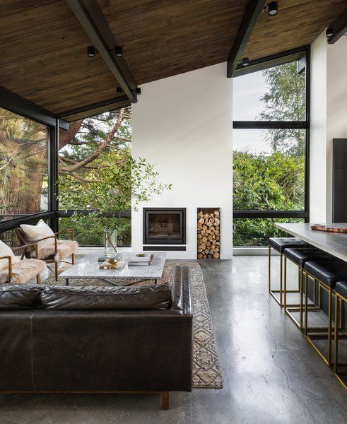 A new double-height fireplace column is the focal point of the new living room and underscores the room's graceful proportions. Tagged: Living Room, Chair, Coffee Tables, Concrete Floor, Sofa, Standard Layout Fireplace, Rug Floor, and Ceiling Lighting.