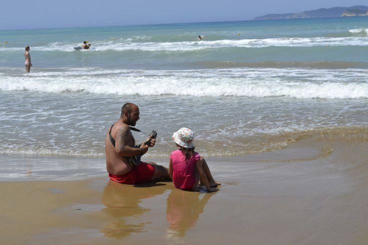 Cute moment of father and daughter on Aghios Stefanos beach.
