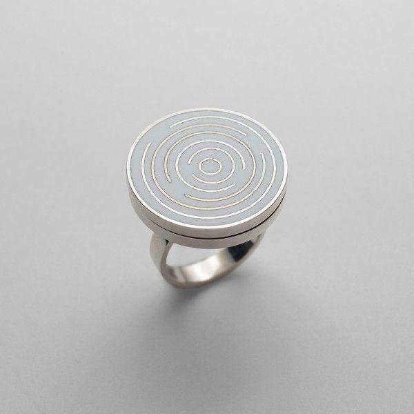 ERMES Anello in argento 925 rodiato con smalto a gran fuoco. Dimensioni cm. 28x25x25, peso gr. 18,1. Questo anello rappresenta uno dei tanti tentativi di semplificare al massimo gli interventi. Forma pura, colore neutro e piccoli segni labirintici per chiudere il cerchio. Anello tra i più silenziosi.