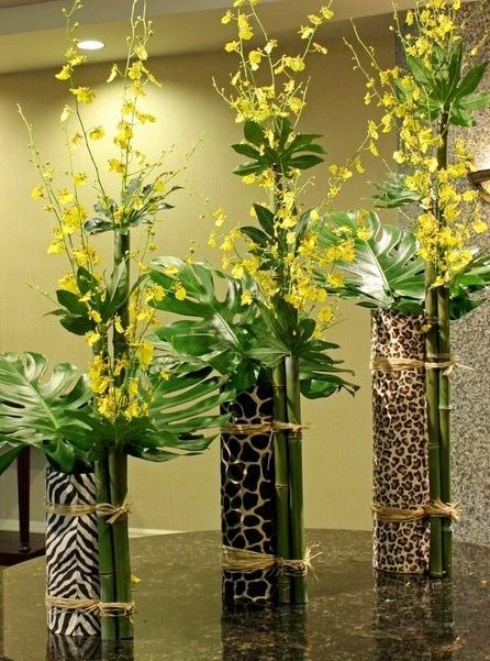 "Fresh cut bamboo are the vases for the delicate oncidium orchids. tied onto jungle print fabric cylinder vases and counterbalanced monstera leaves. ""Jungle Fever"""