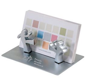 """Magnetic Figurines Card Holder Size: 3.75"""" x 2.4"""" x 1.3"""" What a whimsical way to display your business cards. Our fun and functional Working Together Business Card Holder is crafted in a polished silver finish and has two silver figurine magnets that can be positioned anywhere on the base to hold your cards. Engrave a short message or name on the plate in your choice of different font styles. This creative desk accessory is the perfect thing to present someone who enjoys…"""