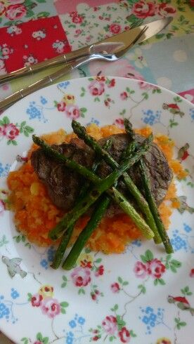 Steak on a bed of carrot and suede served with asparagus