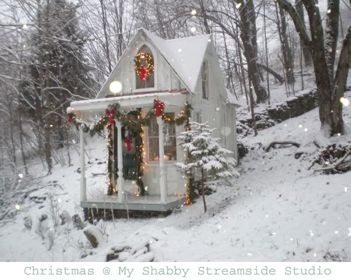 little white cottage in the woods decorated for christmas