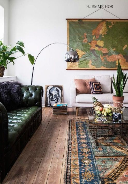 Gorgeous living room with green leather couch, oversized art, and traditional rug