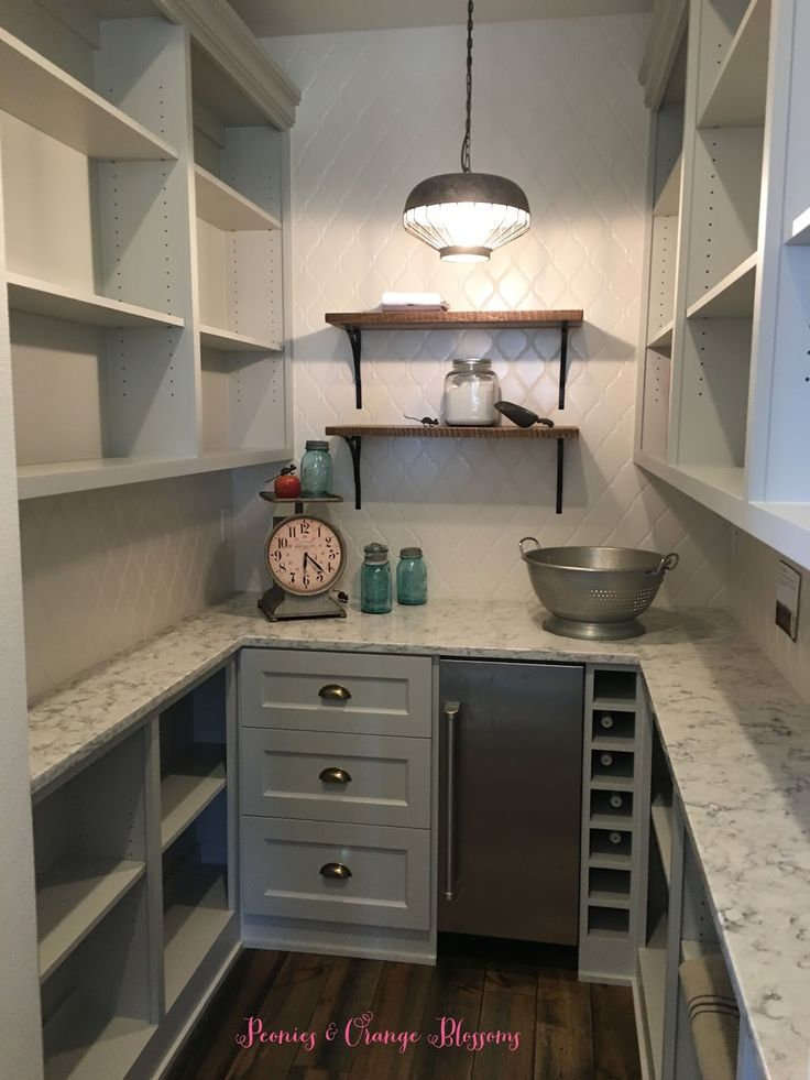 Farmhouse pantry with grey cabinets, white tile, open shelving, marble counters