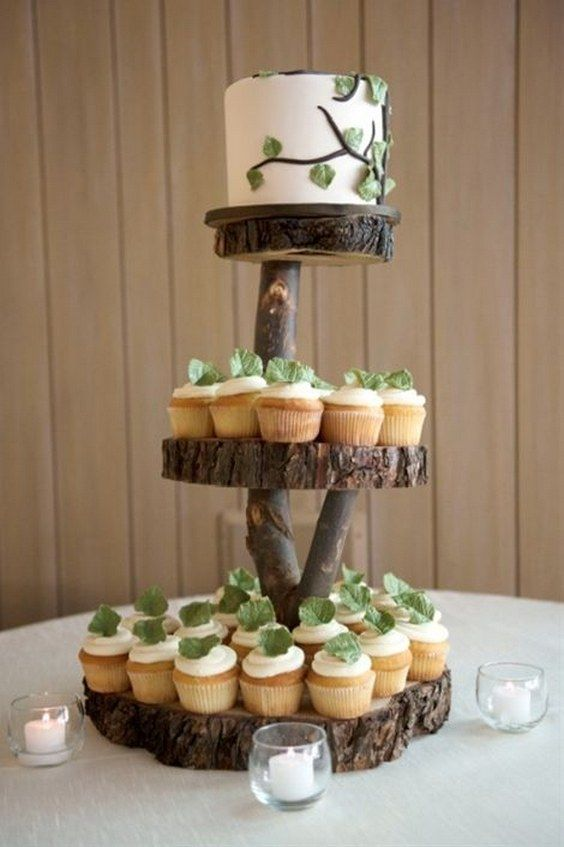 Wedding cupcakes and a cutting cake displayed on wooden tree slices