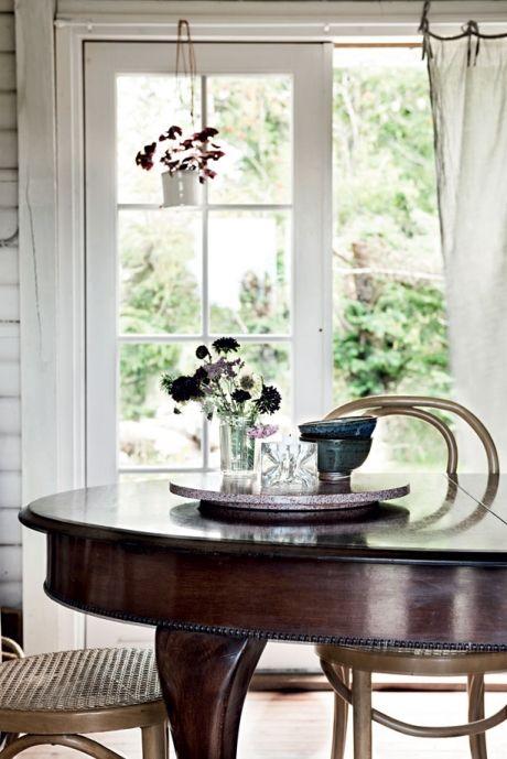 Det fine, gamle spisebord er husets navle, herfra kan man se alle værelser og haven på begge sider. Bordet har Camilla arvet fra sin farmor, og det er en af de ting, der er fundet frem fra kælderen, mens stolene er købt til stedet på Lauritz.com. Den hængende skjuler i vinduet er fra Anne Black.
