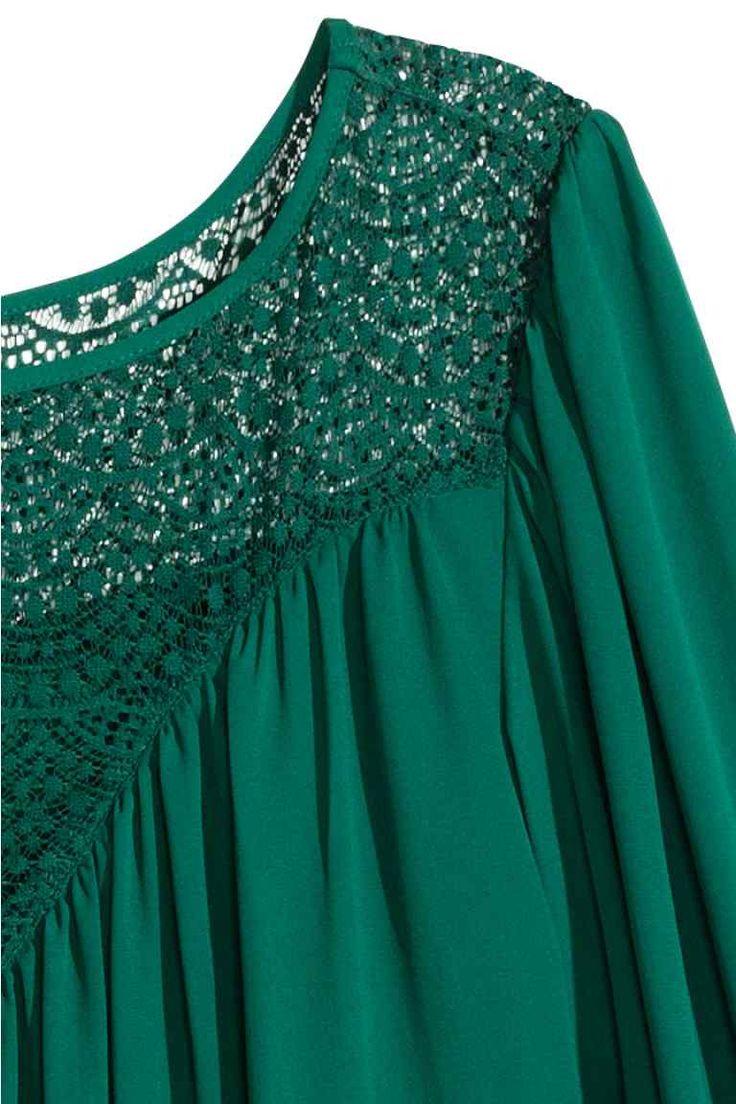 Robe avec dentelle: Robe tissée, courte et évasée. Modèle avec empiècement d'épaules en dentelle et longues manches bouffantes terminées par bouton. Doublée jersey.