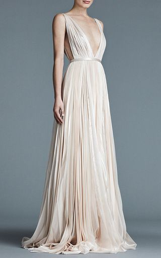 This **J. Mendel** Kaia gown, rendered in lurex chiffon, features a plunge v-neck, an A-line waist, pleating throughout, an exaggerated front split and a short train. Please note: v-neck will be more shallow in production.