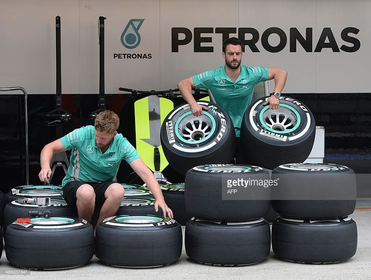 Mercedes AMG Petronas pit crew members prepare tyres for their drivers Nico Rosberg of Germany and Lewis Hamilton of Britain before the upcoming the Formula One Chinese Grand Prix in Shanghai on April 16, 2014. The Formula One Chinese Grand Prix in Shanghai runs from 17-20 April. AFP PHOTO/Mark RALSTON