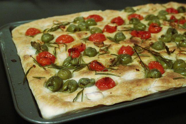 """Pentru a afla istoria pâinicii italienești numită focaccia, trebuie să descindem mult în timp, până în vremea Imperiului Roman, când această pâine plată, destul de asemănătoare cu pizza, era pregătită în cenușa cuptoarelor în care se făcea focul. De altfel, exact de aici își trage și numele: focaccia vine din latinescul """"focacius"""", care înseamnă """"cuptor"""" …"""
