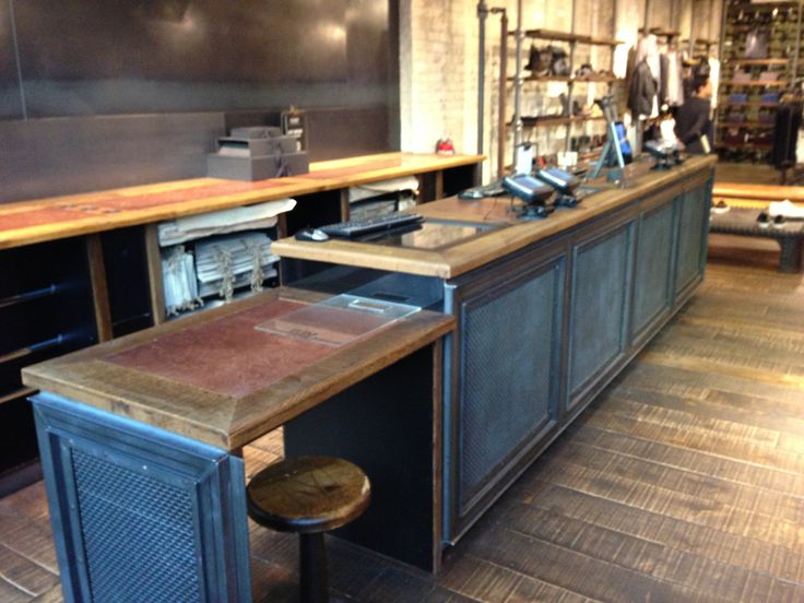 All Saints cash wrap - industrial style. Computer screens are tucked under the cabinet top and visible through the glass inserts. Counter is used for minimal merchandise display.