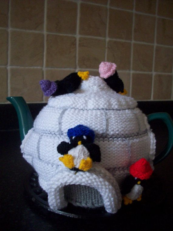 A RosieCosie by Linda Rose    This is my own design using a range of yarns and stitch techniques to create a unique a  and cute Igloo with all the penguins having fun around it. Finished using applique and embroidered detail. Knitted in chunky yarn to create a cuddly and cute appearance as well as proving extra insulation to keep your tea warm for longer. The penguins are all lightly stuffed (BS5852). This would be a loveable addition to the tea table Christmas Eve or any time of…