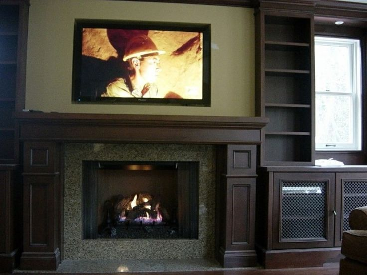TV over fireplace with built-in cabinet next to hearth ...