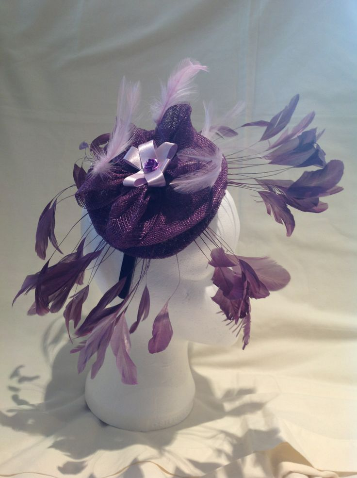 A fascinator by fascinators by Julie the Charlotte is a large fascinator on a black head band with a large amethyst sinamay base the centre piece is a lilac ribbon flower with a small amethyst flower in the centre surrounded by amethyst leaves and matching flowers. $130 AUD. Found in the amethyst and lilacs collection on the website.