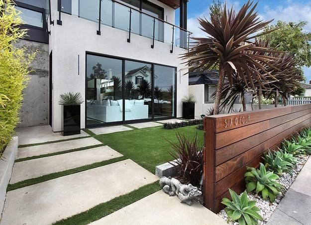 modern front floating wood wall with evenly spaced agave attenuata, pavers with grass modernize the lawn, love tall plant rising behind wall