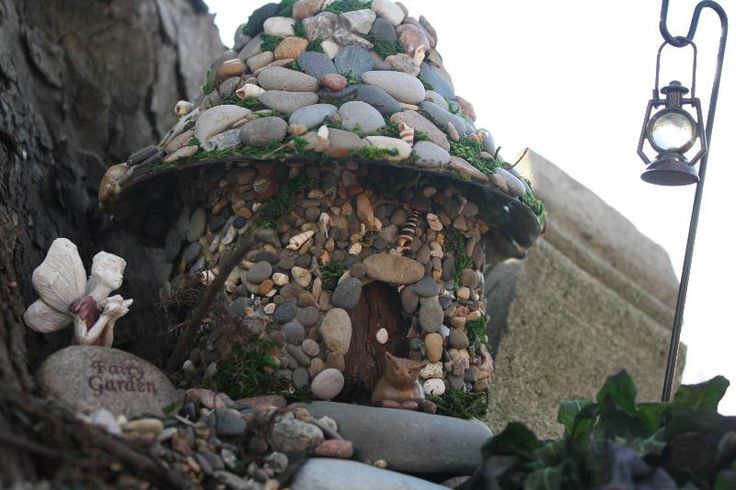 In my fairy garden. Stone and beach pebble over an old plastic juice bottle and a plastic salad bowl for a roof.