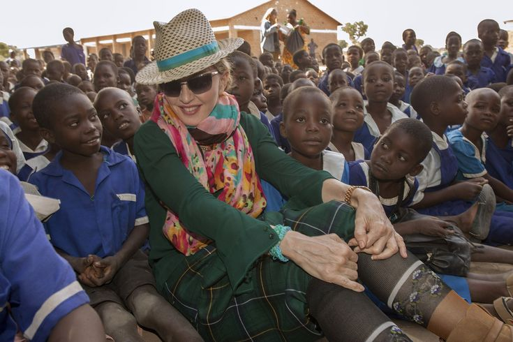 US pop diva Madonna sits among Malawian children during a visit to the Mkoko Primary School, one of the schools Madonna's Raising Malawi organization has built jointly with US organization BuildOn in the Kasungu District, Central Malawi, on November 30, 2014. Madonna met Malawi's new president on November 28 after her VIP status was restored in the country where she adopted two children but then fell foul of the former government. Madonna has adopted two children from the country, which…