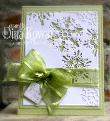 handmade winter card from Mama Dini's Stamperia: Snowflake dies ... soft moss green and white .. luv how die cut snowflakes are used for negative space and as texture for white on white look ... perfect triple loop bow in chiffon with satin edging ... gorgeous card!