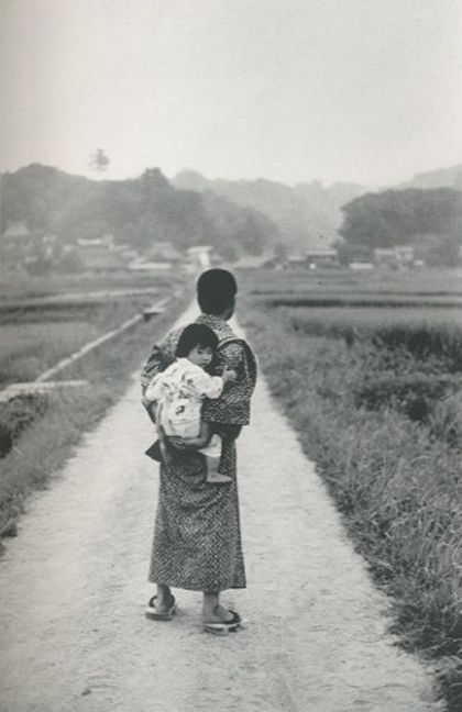 Japanese man in kimono, in the countryside, with a baby on his back. Japan. Early 20th century?