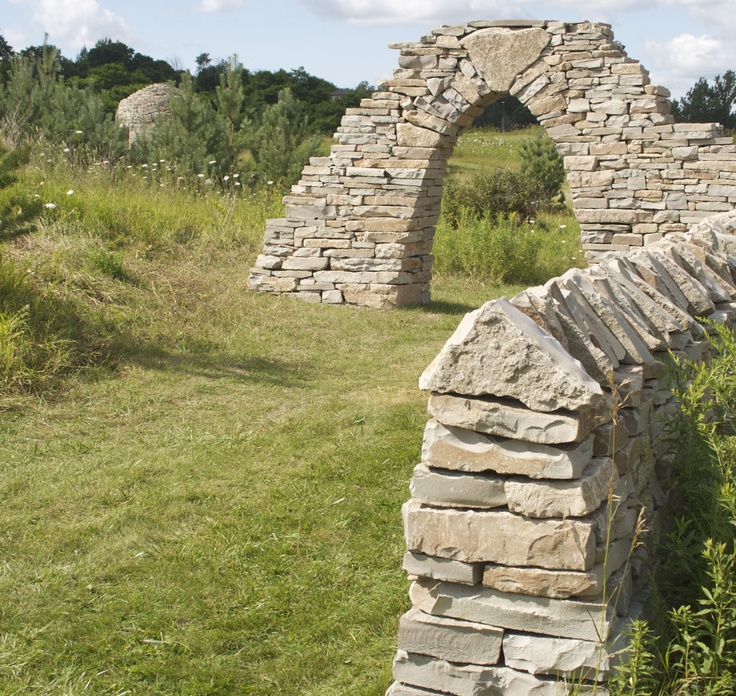 Free standing arch, dry stone wall and beehive hut in the
