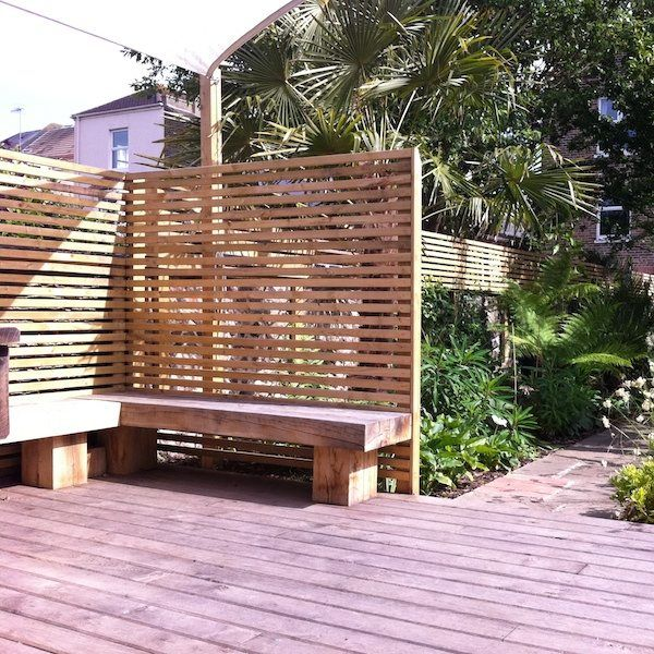 Raised wooden deck with solid oak benches surrounded by a wooden trellis