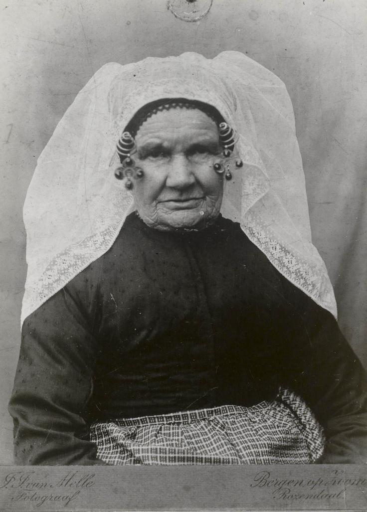 Arbeidersvrouw in Noord-Bevelandse streekdracht, circa 1900. De vrouw draagt een 'lange muts' met machinale, zogenaamde 'halve kant' (smal) en 'halve steenbellen' aan de krullen van haar oorijzer. #NoordBeveland #Zeeland