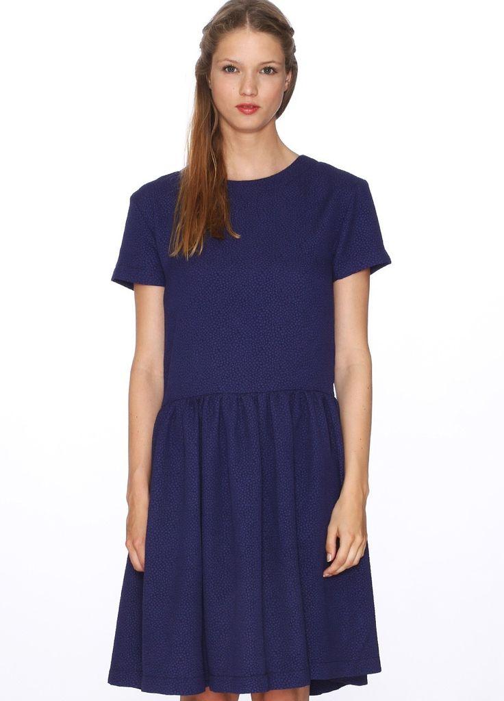 Vestido de manga corta, falda corte a la cadera de vuelo fruncida. Cuello redondo, tela con textura. Color azul marino