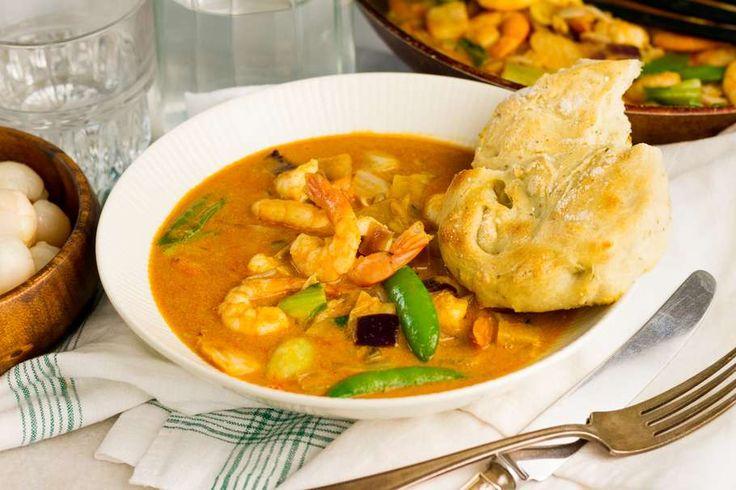 Recept voor garnalencurry voor 4 personen. Met zonnebloemolie, zout, peper, bakpapier, currypasta, garnaal, kokosmelk, lychee, oosterse roerbakgroente, knoflook, volle yoghurt en bloem