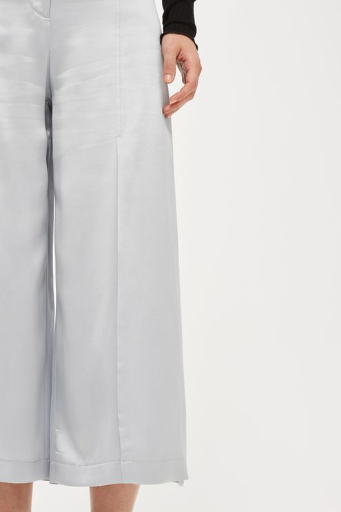 Opt for an effortless, sleek feel to your look with these cropped wide trousers in sand washed silk. In a striking silver hue, they come with pleat detail to the front. Pare it back with a black knit for a contrasted look.