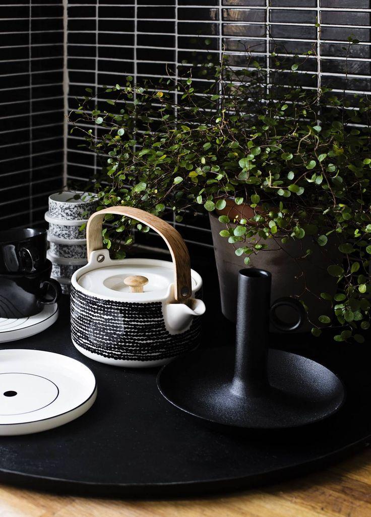 Musta pitkulainen laatta on kuin 60-luvulta. Vuokraemännän valitsema laatta on myös Sannin ja Joonan mieleen. Valikoima mustavalkoisia esineitä muodostaa eheän ryhmän. Teepannu on Marimekon, kynttilänjalka Ikeasta, Design House Stockholmin lautaset Sisustuksen Koodista. Mustat mukit ovat kirpputorilta hankittua vanhaa Kiltaa. Kuviolliset mukit ovat Arabian kirpputorilöytöjä ja tarjottimen Sanni on takonut itse. Tarjotin on osa Sannin suunnittelemaa sohvapöytää.