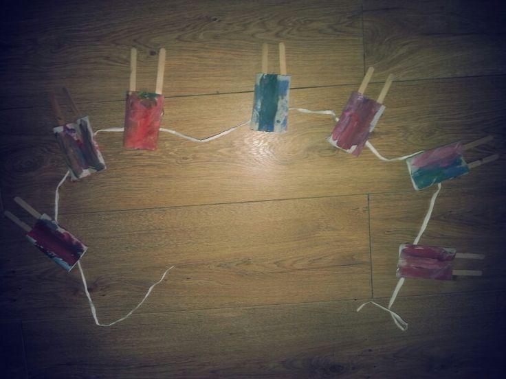 Thema zomer: decoratieve slinger van ijsjes. Niet  het midden van een wc rol vast. Verven, ijsstokjes erin plakken en klaar;)