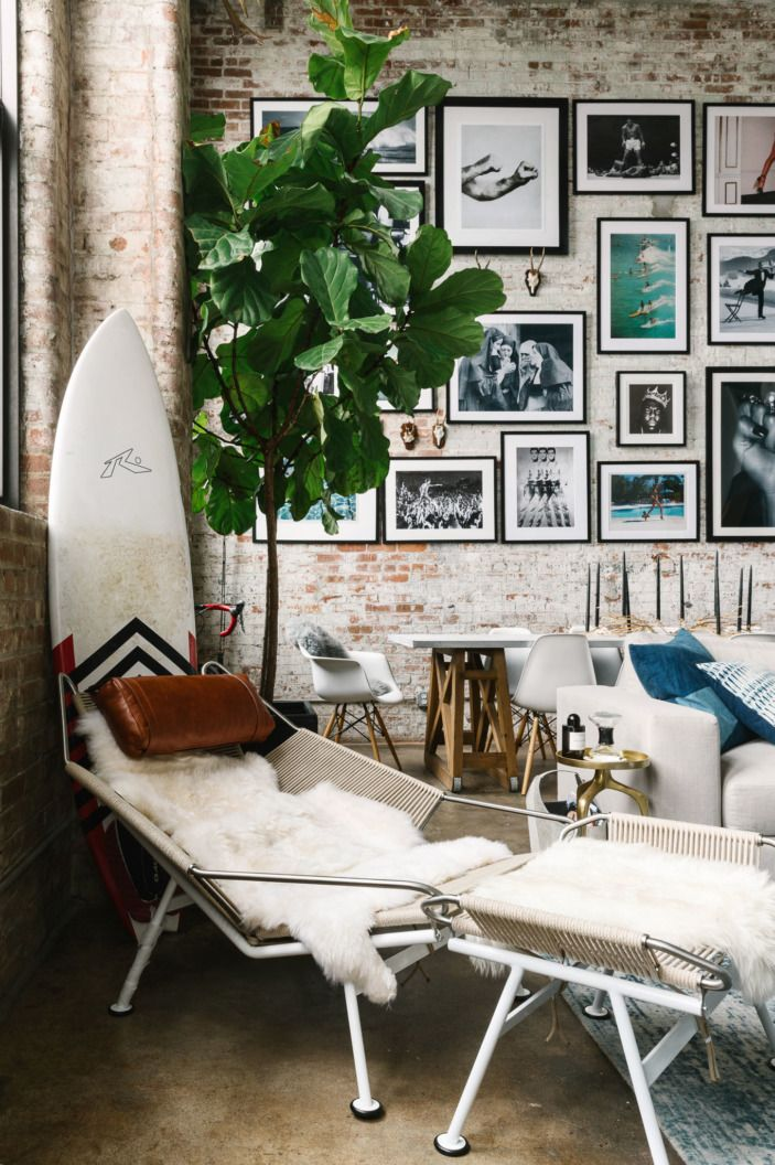 The apartment balances elegance with quirk, like this corner with a Hans Wegner lounger matched with a surfboard.
