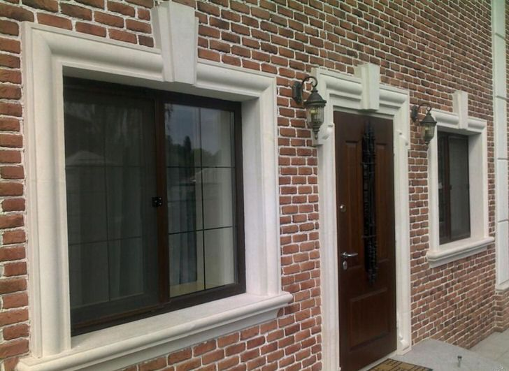Кирпичная кладка органично сочетается с фасадной лепниной, обрамляющей оконные и дверные проемы.