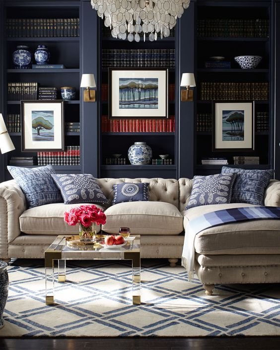 This linen Chesterfield Sectional Sofa pops against the lacquered built-ins in this classic & preppy navy and white space. |  Source: Horchow