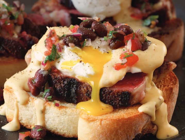 Thickly sliced Texas toast, slathered with garlic butter and grilled until golden brown, is home base for a black bean tomato relish, gorgeous strips of flavorful grilled rib eye, a perfectly poached egg, and a gilding of luscious hollandaise-meets–steak sauce.