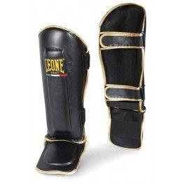 Protège tibia Boxe en cuir Thai-Style Leone1947 Noir & Or Moulé dans le Style traditionnel thaïlandais, ces protèges-tibias élites, sont un complément parfait pour les athlètes professionnels et amateurs. Deux niveaux de mousses au niveau du tibia et du cou-de-pied profilées fournissent une absorption de choc et de la protection maximale.
