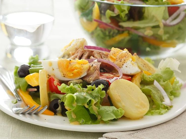 A salad of green beans, potatoes, hard-boiled eggs, tomatoes, anchovies, tuna, and olives.