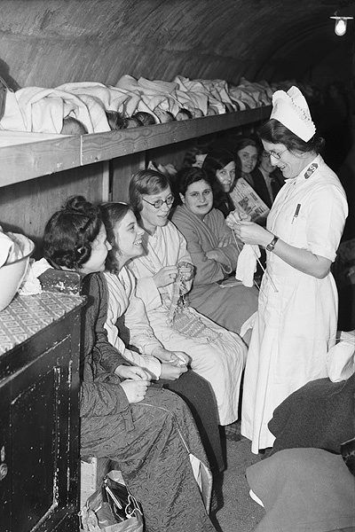 Mothers knitting in an air raid shelter, with a shelf of babies above them. London, 1940