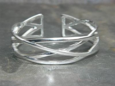 For a small wrist. A fascinating silver metal bracelet that has a wide criss cross pattern. Modern and stylish, this cuff will dress up jeans, or look great at a dressy party.