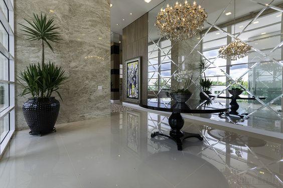 Hall de entrada com pé direito alto , recebeu uma parede de espelhos com placas diagonais bisotadas.  http://conexaodecor.com/2017/05/parede-de-espelhos/