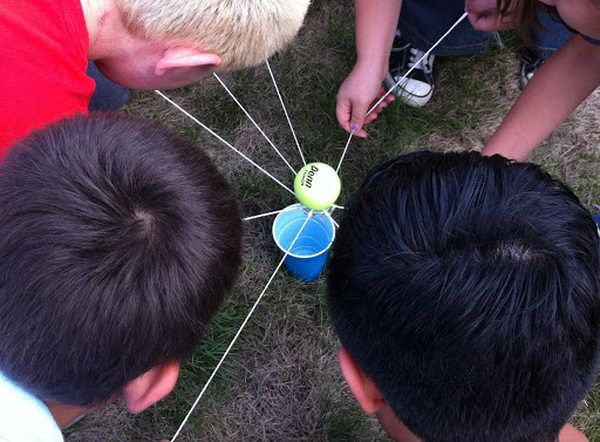 Soccer Ball Transfer Team Building- Balance a ball on a ring held by strings. Groups have to hold the strings while walking to transfer balls to a box.