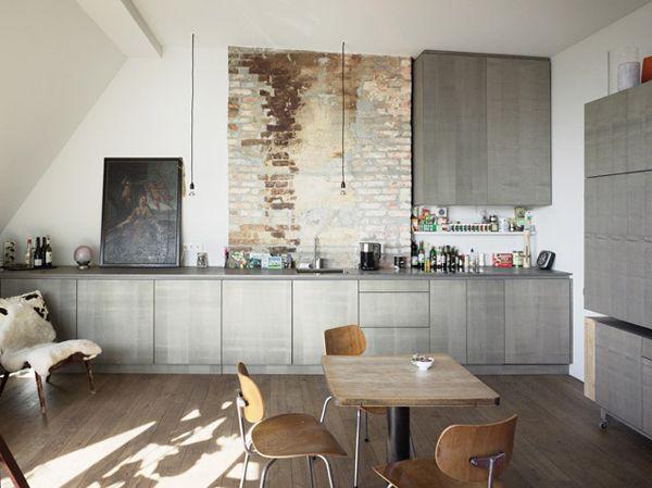 Grijze keuken met ruwe bakstenen en houten vloer