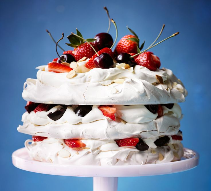 This Pavlova cake, topped with strawberries, cream, cherries and almonds, makes an impressive dinner party dessert