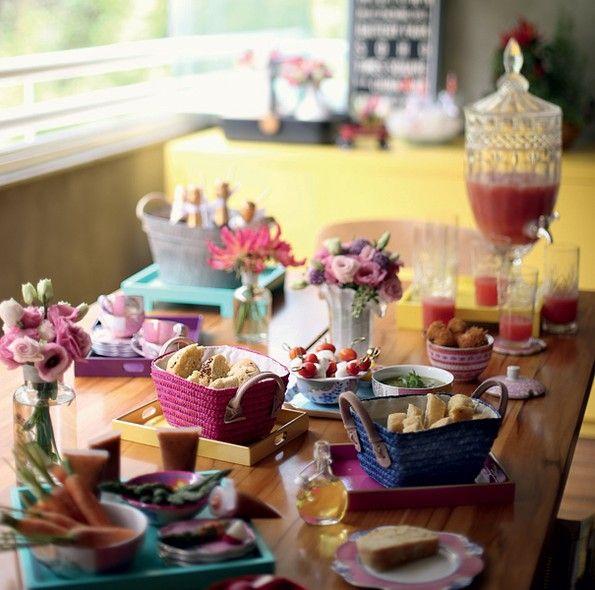 Cestinhas com pães caseiros, suqueira, copos e bowls foram colocados sobre bandejas coloridas, que alegraram a mesa e evitaram manchas na madeira