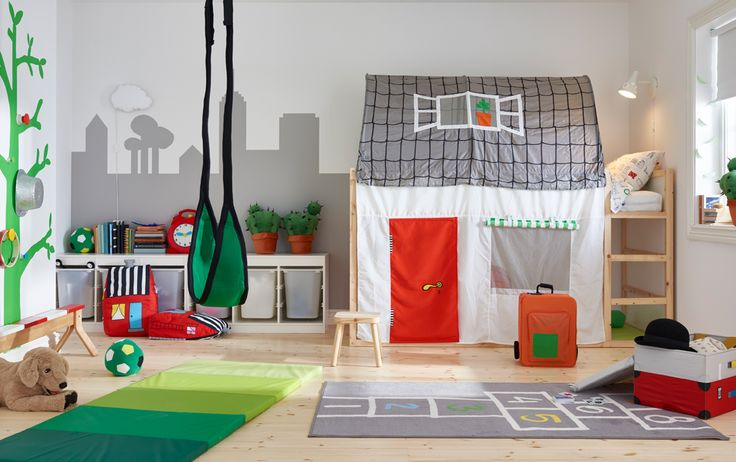 Ein bunt eingerichtetes Kinderzimmer mit umbaufähigem KURA Bett in Weiß/Kiefer und KURA Baldachin/Bettvorhang in Hausform in Grau/Weiß und vielen Spielen für draußen