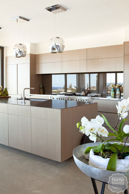 NAV Enviroven™ Driftwood veneer cabinetry covers the island bench and cupboards, while a smoky grey glass splashback offsets the honed-marble and stainless-steel work surfaces.