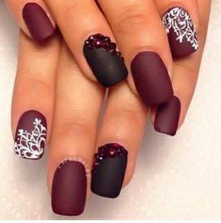 Burgundy nails with white designs and the accent nail in black with red studs